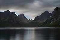 Steep mountain peaks rise above the isolated village or Kirkefjord, Moskenesøy, Lofoten Islands, Norway