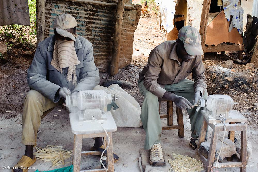 Local craftsmen grind wood and stone materials, Kibera slum, kenya