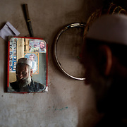 November 06, 2012 - Kabul, Afghanistan: Reflexion of a local merchant on a mirror in a shop at the bird's bazaar. In the back wall, posters of the late mujahideen commander, Ahmad Shah Massoud. (Paulo Nunes dos Santos)
