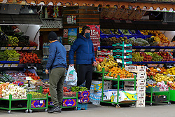 © Licensed to London News Pictures. 25/12/2020. London, UK. A shopper leaves a fruit and vegetable shop in north London, which is open on Christmas Day. Photo credit: Dinendra Haria/LNP
