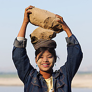 Woman carries and balances rocks on her head for a small salary. Smiling 2 big rocks