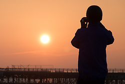 © Licensed to London News Pictures. 23/10/2016. Southsea, UK.  A cyclist stops to capture the sunrise over South Parade Pier in Southsea this morning, where the Great South Run 2016 event is being held today.  Photo credit: Rob Arnold/LNP