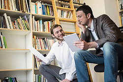 Two businessmen looking at notes and using digital tablet in an office, Bavaria, Germany