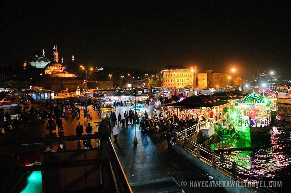 The waterfront of the Eminonu next to the Galata Bridge in Istanbul at night. People come to the area for the fish sandwiches cooked on boats moored against the docks.