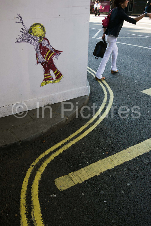 A woman hails a taxi in a London street that has been visited by the cartoon graffiti street artist Nathan Bowen of fireman created outside Shaftesbury Ave fire station. Striking a similar pose as the cartoon character, she also raises her arm to make a humourous street moment. But there is also another visual pun of the double-yellow parking lines endemic in the capitals that are echoed in the cartoon's high-visibility clothing.