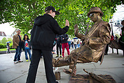 Gravity defying gold street performer entertains people on the riverside walkway. The South Bank is a significant arts and entertainment district, and home to an endless list of activities for Londoners, visitors and tourists alike.