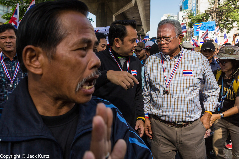 """15 JANUARY 2014 - BANGKOK, THAILAND: A security guard (left) cuts a path through the crowd for SUTHEP THAUGSUBAN (right), former Deputy Prime Minister of Thailand and leader of the Shutdown Bangkok anti-government protests, talks to supporters on Sukhumvit Road in Bangkok during a protest march. Tens of thousands of Thai anti-government protestors continued to block the streets of Bangkok Wednesday to shut down the Thai capitol. The protest, """"Shutdown Bangkok,"""" is expected to last at least a week. Shutdown Bangkok is organized by People's Democratic Reform Committee (PRDC). It's a continuation of protests that started in early November. There have been shootings almost every night at different protests sites around Bangkok. The malls in Bangkok are still open but many other businesses are closed and mass transit is swamped with both protestors and people who had to use mass transit because the roads were blocked.    PHOTO BY JACK KURTZ"""