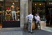 Two young men enjoy drinks outside a pub next to stylishly-dressed menswear mannequins on Lime Street in the City of London, the capitals historic financial district, on 2nd August 2018, in London, England.
