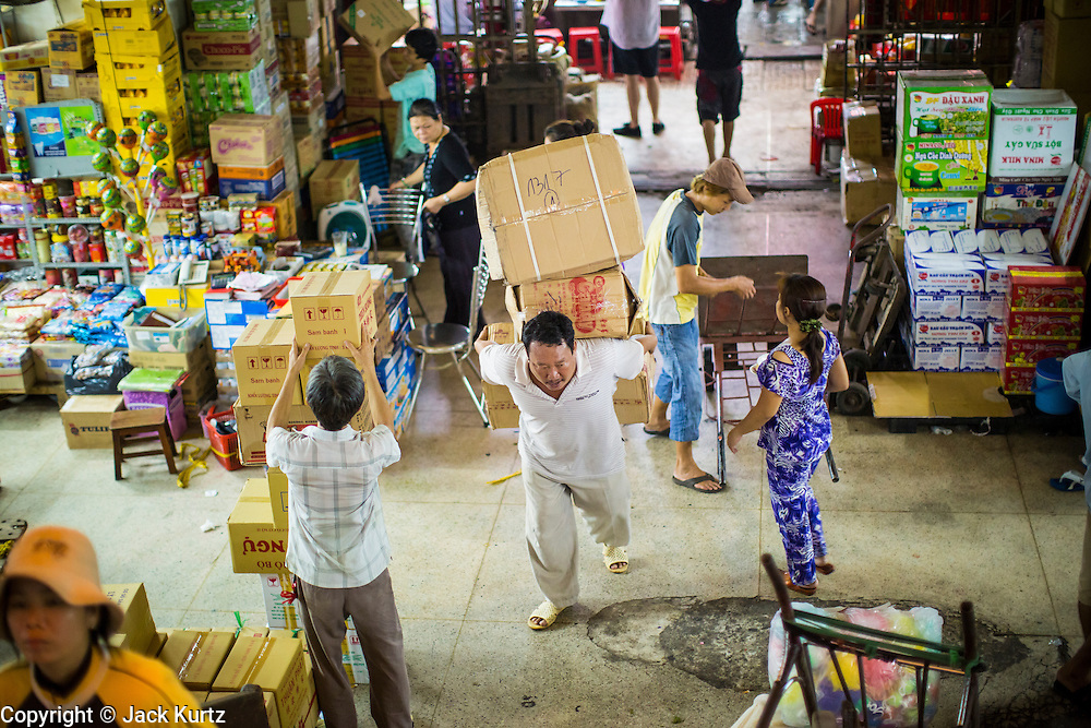 """12 APRIL 2012 - HO CHI MINH CITY, VIETNAM:   A porter makes a delivery in Binh Tay Market. The market is warren of narrow halls and alleys and steep staircases and still relies on manual labor to move goods. Binh Tay market is the largest market in Ho Chi Minh City and is the central market of Cholon. Cholon is the Chinese-influenced section of Ho Chi Minh City (former Saigon). It is the largest """"Chinatown"""" in Vietnam. Cholon consists of the western half of District 5 as well as several adjoining neighborhoods in District 6. The Vietnamese name Cholon literally means """"big"""" (lon) """"market"""" (cho). Incorporated in 1879 as a city 11km from central Saigon. By the 1930s, it had expanded to the city limit of Saigon. On April 27, 1931, French colonial authorities merged the two cities to form Saigon-Cholon. In 1956, """"Cholon"""" was dropped from the name and the city became known as Saigon. During the Vietnam War (called the American War by the Vietnamese), soldiers and deserters from the United States Army maintained a thriving black market in Cholon, trading in various American and especially U.S Army-issue items.        PHOTO BY JACK KURTZ"""