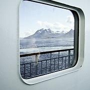 Three weeks aboard the Kong Harald. Hurtigruten, the Coastal Express. Woman looking the landscape through a window.