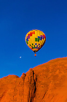 Hot air balloon flying in front of a huge monolithic rock during the Red Rock Balloon Rally, Red Rock State Park, near Gallup, New Mexico USA.