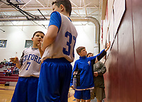 Members of the Gilford boys 5th and 6th grade team checks the Francoeur Babcock 26th memorial basketball tournament bracket board as they advance to the next round with a win over Belmont on Saturday afternoon.  (Karen Bobotas/for the Laconia Daily Sun)