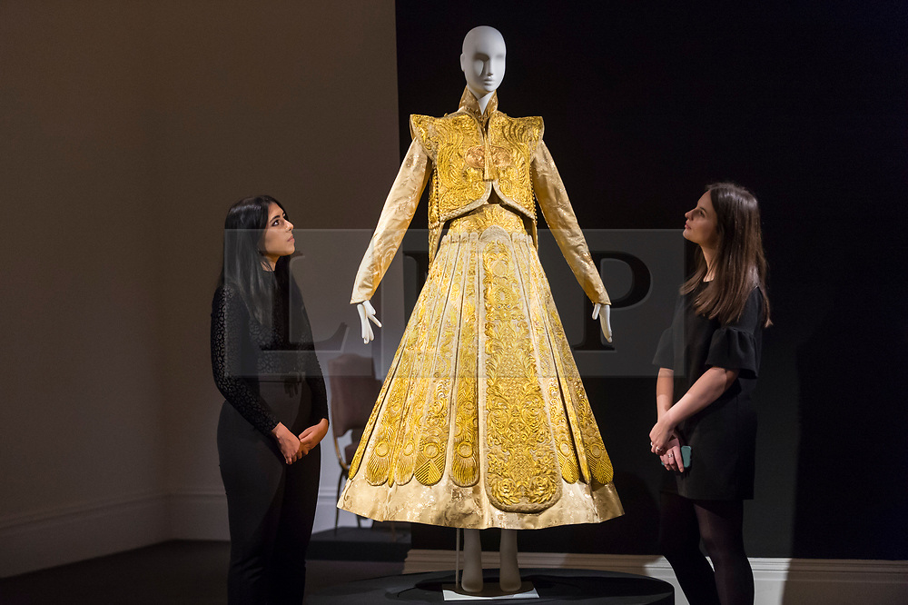 """© Licensed to London News Pictures. 25/10/2019. LONDON, UK. Staff members pose with a """"Gold Chinese traditional bridal dress"""" by Guo Pei (Est.  GBP500-700k).  Preview of """"GOLD: The Midas Touch"""" at Sotheby's in New Bond Street.  Artworks spanning six centuries dedicated to gold will be offered for sale on 29 October.  Photo credit: Stephen Chung/LNP"""