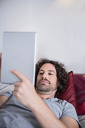 Man lying down on couch and using a digital tablet, Munich, Bavaria, Germany