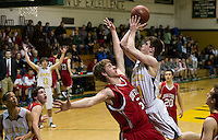 John Stark's Zachary Grattan attempts to block Bishop Brady's Stephen Desmarais' shot during first round NHIAA Division II tournament action Wednesdy.  (Karen Bobotas/for the Concord Monitor)