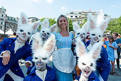 © Licensed to London News Pictures. 18/07/2021. LONDON, UK. Actors dressed as Alice (as the white queen) and white rabbits (as pawns) arrive at Chess Fest in Trafalgar Square.  The event celebrates the game of chess and visitors can learn the game, play chess or challenge a Grandmaster.  Also, to celebrate the 150th anniversary of Lewis Carroll's Alice Through the Looking Glass book which featured the game of the chess, 32 actors dressed as Alice Through the Looking Glass characters stand on a giant chessboard replaying a game based on the book.  Photo credit: Stephen Chung/LNP