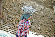 A woman labourer carrying concrete on a building site in Mandalay on 25th May 2016 in Myanmar
