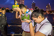28 NOVEMBER 2012 - BANGKOK, THAILAND:  School children pray before launching their krathongs on Loy Krathong at Wat Yannawa in Bangkok. Loy Krathong takes place on the evening of the full moon of the 12th month in the traditional Thai lunar calendar. In the western calendar this usually falls in November. Loy means 'to float', while krathong refers to the usually lotus-shaped container which floats on the water. Traditional krathongs are made of the layers of the trunk of a banana tree or a spider lily plant. Now, many people use krathongs of baked bread which disintegrate in the water and feed the fish. A krathong is decorated with elaborately folded banana leaves, incense sticks, and a candle. A small coin is sometimes included as an offering to the river spirits. On the night of the full moon, Thais launch their krathong on a river, canal or a pond, making a wish as they do so.   PHOTO BY JACK KURTZ