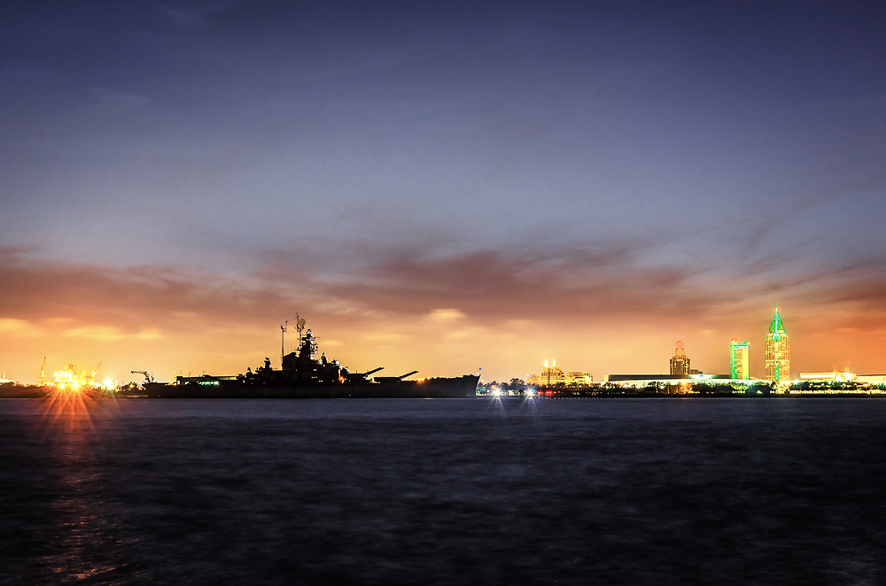 USS Battleship in front of Mobile skyline. Mobile has flown under the French, Spanish, British, Republic of Alabama, Confederacy, and the USA flags.<br /> Today Mobile is one of the fastest growing metro area in the United States. In 2010 Mobile's Alabama State Docks had increase container storage at the docks by over 1,000%.
