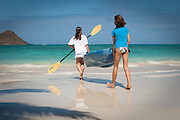 Two girls carrying a kayak at Lanikai Beach on Oahu, Hawaii.