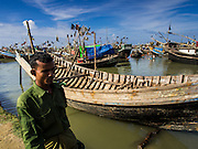 07 NOVEMBER 2014 - SITTWE, RAKHINE, MYANMAR: A Rohingya Muslim man walks past a boat being refurbished in the port of a Rohingya IDP camp near Sittwe. The government of Myanmar has forced more than 140,000 Rohingya Muslims who used to live in Sittwe, Myanmar, into squalid Internal Displaced Person (IDP) camps. The forced relocation took place in 2012 after sectarian violence devastated Rohingya communities in Sittwe and left hundreds dead. None of the camps have electricity and some have been denied access to regular rations for nine months. Conditions for the Rohingya in the camps have fueled an exodus of Rohingya refugees to Malaysia and Thailand. Tens of thousands have put to sea in rickety boats hoping to land in Malaysia but sometimes landing in Thailand. The exodus has fueled the boat building boom on the waterfront near the camps. Authorities expect the pace of refugees fleeing Myanmar to accelerate during the cool season, December through February, when there are fewer storms in the Andaman Sea and Bay of Bengal.   PHOTO BY JACK KURTZ