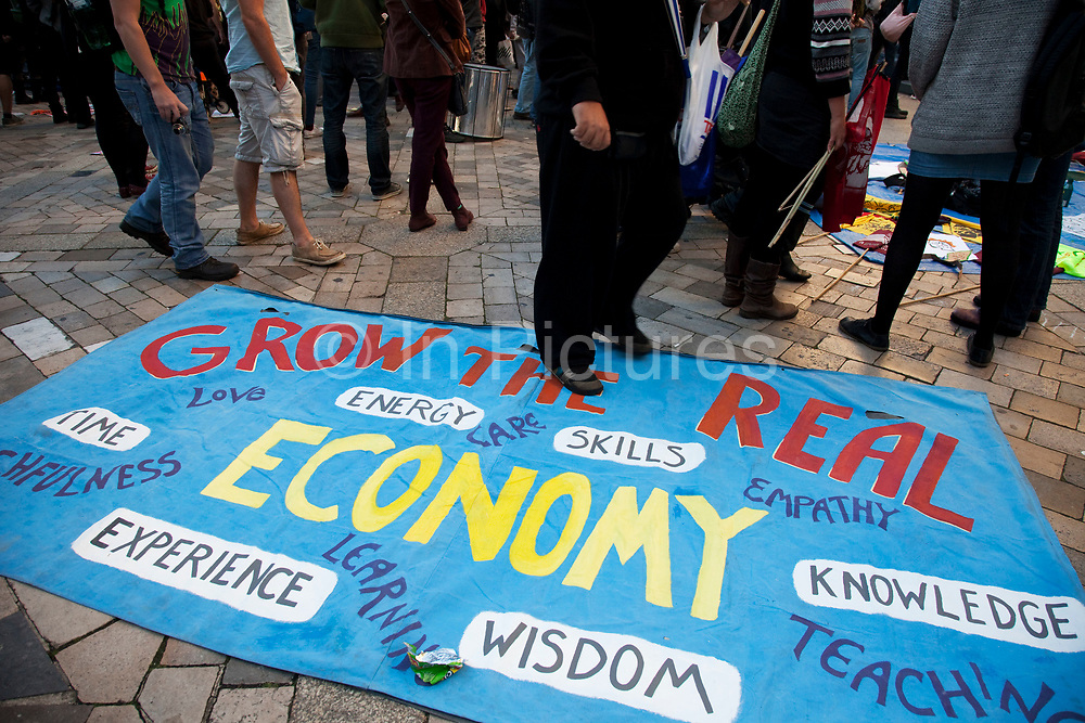 """Occupy London protest at St Pauls, October 15th 2011. Protest spreads from the US with this demonstrations in London and other cities worldwide. The 'Occupy' movement is spreading via social media. After four weeks of focus on the Wall Street protest, the campaign against the global banking industry started in the UK this weekend, with the biggest event aiming to """"occupy"""" the London Stock Exchange. The protests have been organised on social media pages that between them have picked up more than 15,000 followers. Campaigners gathered outside  at midday before marching the short distance to Paternoster Square, home of the Stock Exchange and other banks.It is one of a series of events planned around the UK as part of a global day of action, with 800-plus protests promised so far worldwide.Paternoster Square is a private development, giving police more powers to not allow protesters or activists inside."""
