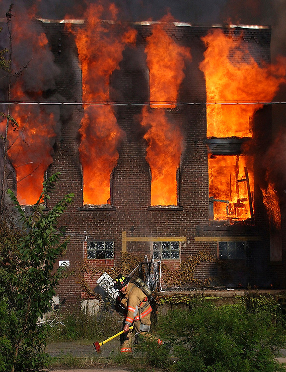 A firefighter picks up an ax as the old Montgomery Mill burns behind him in Windsor Locks, Conn.