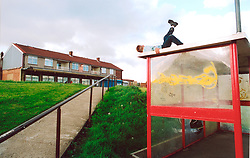 Boy playing on top of bus shelter; Bradford council estate; UK