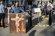 Satrical artist Kaya Mar with his latest painting depicting Prime Minister Boris Johnson on a cross being crucified as media gather outside the Supreme Court on day three of the hearing to rule on the suspension of parliament. Supreme Court judges will decide if Prime Minister Boris Johnson acted unlawfully in advising the Queen to prorogue parliament, on September 19th 2019 in London, United Kingdom.