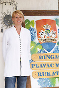 Mrs Matusko, from Germany, married to Mato Violic Matusko, the winemaker, outside the winery with a sign with the wine names and the coat of arms with a crown, two donkeys' heads bunch of grapes. Matusko Winery. Potmje village, Dingac wine region, Peljesac peninsula. Matusko Winery. Dingac village and region. Peljesac peninsula. Dalmatian Coast, Croatia, Europe.