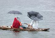People shelter from rain on their shikara, a local wooden boat, on Lake Dal, Srinigar, Kashmir, India