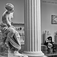 An Ancient Roman Muse tries to peek around a column to see what that glowing thing is the young woman is staring at; Metropolitan Museum of Art.