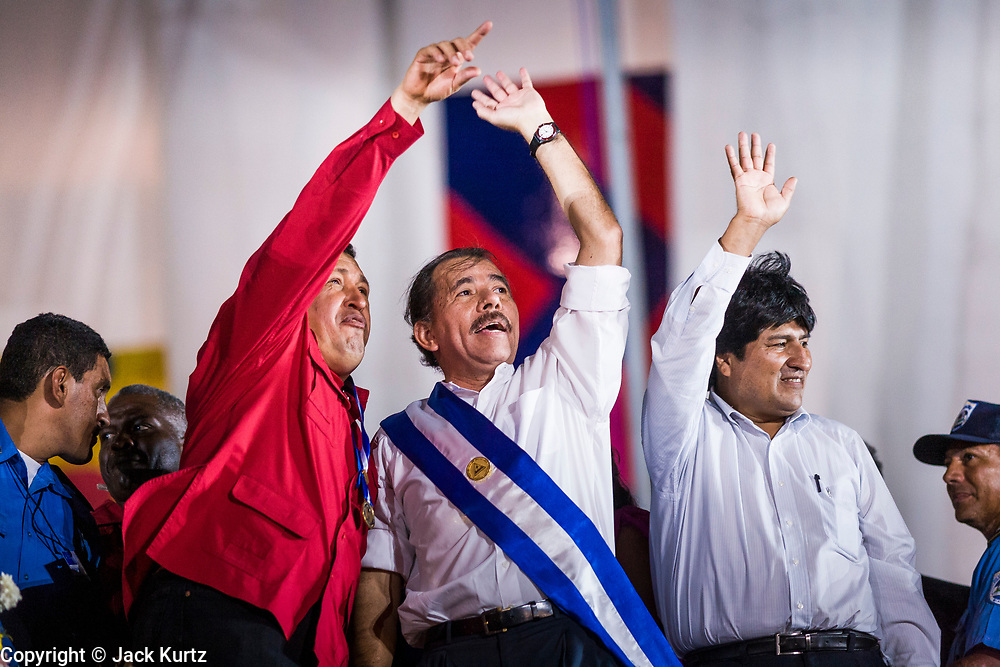 """10 JANUARY 2007 - MANAGUA, NICARAGUA: HUGO CHAVEZ, President of Venezuela, left, DANIEL ORTEGA, President of Nicaragua, and EVO MORALES, President of Bolivia, wave to the crowd during Ortega's inaugural speech in Managua.  Daniel Ortega, the leader of the Sandanista Front, was sworn in as the President of Nicaragua Wednesday. Ortega and the Sandanistas ruled Nicaragua from their victory of """"Tacho"""" Somoza in 1979 until their defeat by Violetta Chamorro in the 1990 election.  Photo by Jack Kurtz"""