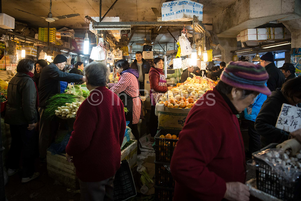 Shoppers and vendors crowd into a fresh food market in Shanghai, China, on Saturday, Dec. 5, 2015.