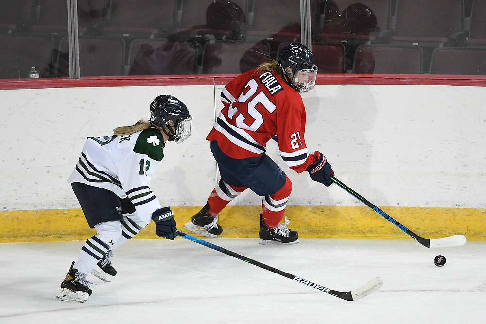 ERIE, PA - MARCH 05: Joelle Fiala #25 of the Robert Morris Colonials skates with the puck under pressure from Megan Korzack #12 of the Mercyhurst Lakers in the first period during the game at the Erie Insurance Arena on March 5, 2021 in Erie, Pennsylvania. (Photo by Justin Berl/Robert Morris Athletics)