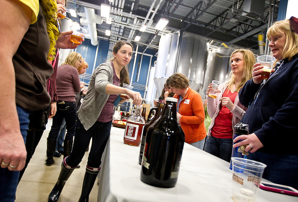 Erica Macke, left, samples a Titletown Brewery growler during Women's Brew Day at Wisconsin Brewing Company in Verona, Saturday, January 24, 2015. The day was filled with education for female brewers from female beer industry experts, discussing malt, hops, beer styles and beer distribution.