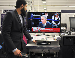 © London News Pictures. 2011/01/21 A shop manager watches Tony Blair on television taking questions at The Iraq Inquiry. Picture credit should read Stephen Simpson/LNP