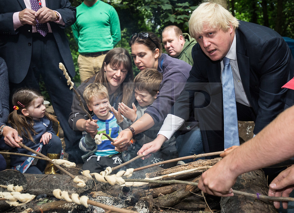 © Licensed to London News Pictures. 30/07/2015. London, UK. The Mayor of London and MP for Uxbridge and South Ruislip Boris Johnson cooking and eating dough on a campfire today during a visit to the Wide Horizons Environment Centre in Bexley where he explored their new outdoor learning centre which was built by an 'army of volunteers' on a once derelict site. Photo credit : James Gourley/LNP