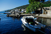 Boat moored at small harbour, town in background. Opatija, Croatia