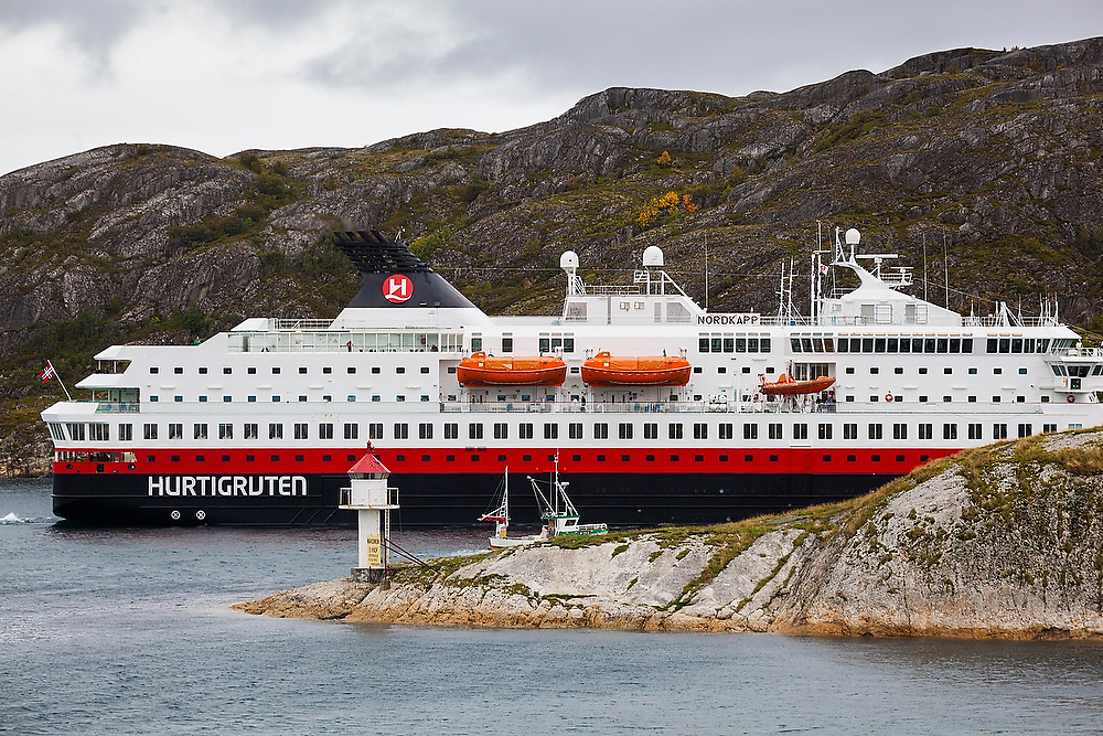 A Hurtigruten cruise ship dwarfs a small fishing boat as they pass side by side through a narrow passage outside Bodo, Norway.