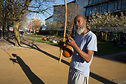 Busker casting his shadow in evening light playing a berimbau. The berimbau, a single-string percussion instrument, a musical bow, from Brazil. The South Bank is a significant arts and entertainment district, and home to an endless list of activities for Londoners, visitors and tourists alike.