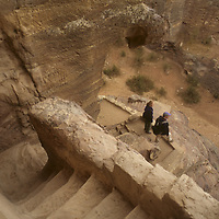 Hikers on ancient Nabataean stairs carved into Jebel [Mount] Madhbah, above Petra, Jordan.