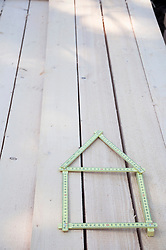 Folding ruler shaped as house on wood