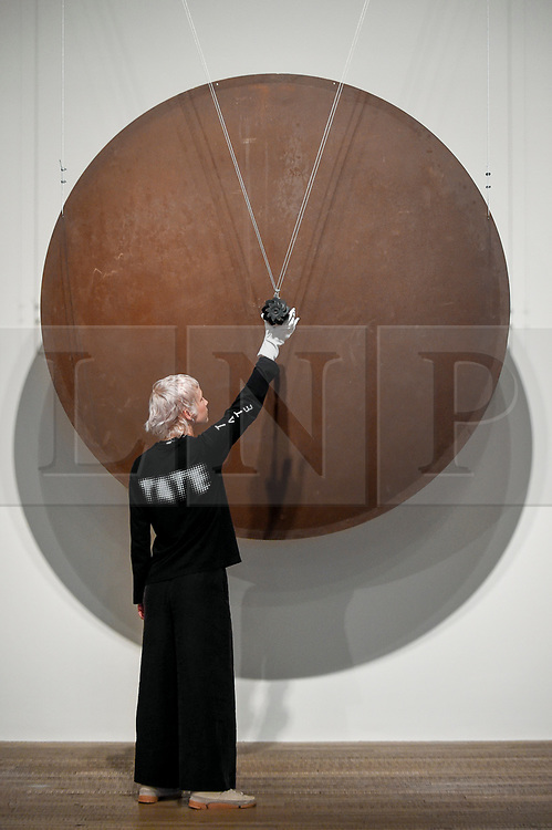 """© Licensed to London News Pictures. 02/07/2019. LONDON, UK.  A staff member with """"Gong"""", 1978, all by Takis. Preview of a new display by the Greek sculptor Takis at Tate Modern.  The retrospective features over 80 works in Takis' largest exhibition in the UK to date and combines works involving magnetism, light and sound.  The show runs 3 July to 27 October.   Photo credit: Stephen Chung/LNP"""