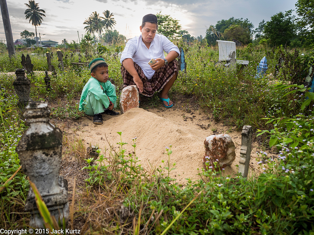 19 JUNE 2015 - PATTANI, PATTANI, THAILAND: A man and his son tend to the grave of the man's father in the Muslim cemetery in Pattani. He said his father died two years ago. The Perkuboran To'Ayah is the Muslim cemetery in Pattani. It is more than 150 years old. The last Sultan of Pattani, who ruled until Siam (Thailand) annexed Pattani is buried in the cemetery. Many victims of political and sectarian violence that has wracked Thailand's three Muslim majority provinces, Pattani, Narathiwat and Yala are also buried in the cemetery. On Fridays, after morning prayers, Muslim men come to the cemetery to tend to the graves of their family members.   PHOTO BY JACK KURTZ