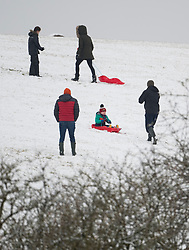 © Licensed to London News Pictures. 28/12/2020. Burford, UK. A group of people sledging on a snow covered hillside, near the village of Burford in Oxfordshire, south England as the UK experiences freezing temperatures over night. Photo credit: Ben Cawthra/LNP