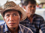 """13 FEBRUARY 2014  - NONTHABURI, NONTHABURI, THAILAND: Thai rice farmers listen to speakers while they occupy the Ministry of Commerce in Nonthaburi, outside of Bangkok. The Thai government instituted a """"rice pledging scheme"""" after the election in 2011. The government agreed to buy farmers' rice crops at above market prices then planned to warehouse the rice and sell it on international markets when prices recovered. At the same time, India and Vietnam started to export large quantities of rice and the Thai government fell short of funds to pay for rice it had already purchased from farmers. Many farmers have not been paid for rice grown in 2013 and some of the rice in the Thai warehouses is allegedly rotting. Thailand has fallen from number 1 rice exporter in the world to number 3 and several government to government contracts the Thais signed with rice importing countries (like China) have been cancelled. Farmers, once key supporters of the government are now joining anti-government protests in Bangkok and occupying government ministries including the Ministry of Commerce.    PHOTO BY JACK KURTZ"""