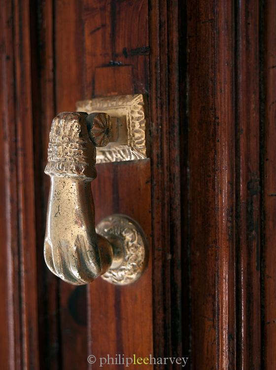 Detail of a brass door knocker on an old wooden door in northern Spain