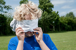 Young blonde boy holding removing blindfold