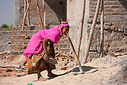 Woman builder carries cement on her head at Khore village, Rajasthan, India